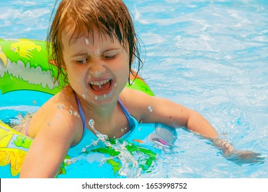 Funny portrait of happy cute little child girl playing in swimming pool.