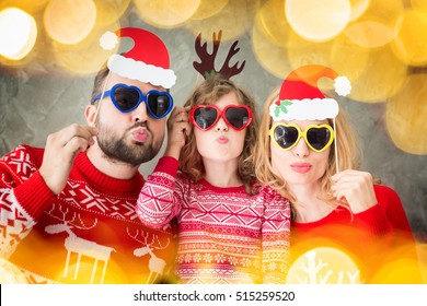 Funny portrait of happy family with Christmas paper props. Mother; father and child having fun together. People playing at home. Winter holiday Xmas and New Year concept