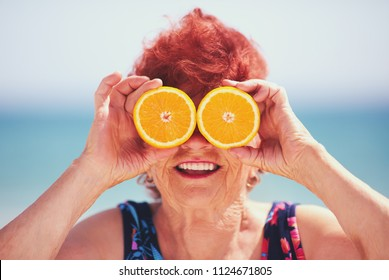 funny portrait of happy mature woman, grandma having fun with orange eyes on summer vacation. Active lifestyle