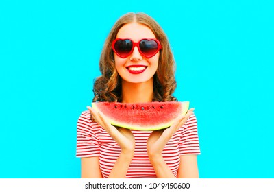 Funny portrait happy smiling young woman holding slice of watermelon over colorful blue background
