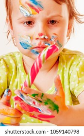 Funny portrait of little cute child girl painted in the face with candy (childhood, happynes, sweets, holiday concept)