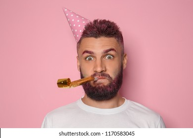 Funny portrait of man with Birthday hat and party whistle on color background