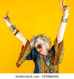 Funny portrait of mature woman. Beautiful lady have fun dressed with seventies costume. Mature woman on colored backgrounds - Shutterstock ID 1950883441