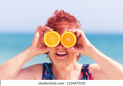 funny portrait of mature woman, grandma having fun with orange eyes on summer vacation