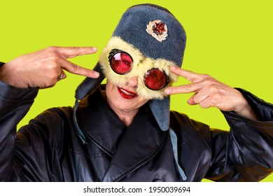 Funny portrait of mature woman. Lady posing dressed as a Russian aviator. Mature woman on colored backgrounds
