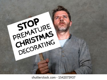 funny portrait of serious and upset attractive man holding hilarious handwritten protest banner against premature Christmas decorating demanding to stop on isolated background