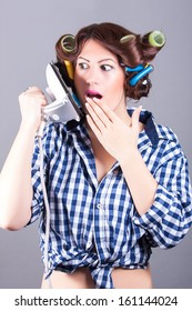 funny portrait of sexy housewife with iron like cell phone