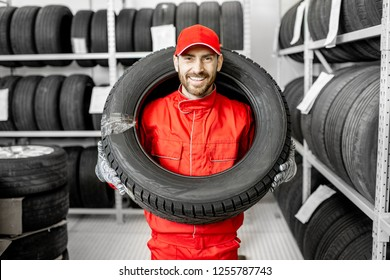 Funny portrait of a smiling worker in red uniform wearing car tire on his head in the warehouse