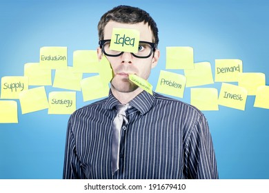 Funny portrait of a stressed business man standing on blue background amongst sticky notes when planning ideas to solve problems
