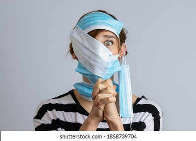 Funny portrait of a stressed woman with whole face covered in surgical masks with hands in prayer position in a gray background