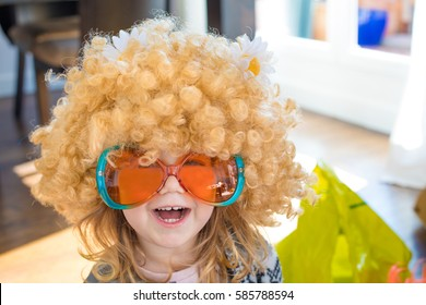 funny portrait of three years old child disguised as sixties, with great curly blond hair wig with daisy flowers on head, with orange and green colorful glasses, looking laughing