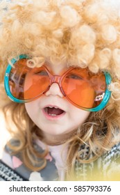 funny portrait of three years old child face disguised as sixties, with great curly blond hair wig on head, with orange and green colorful glasses, looking speaking