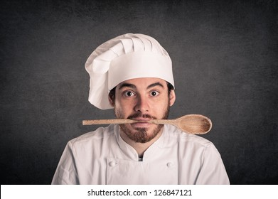 Funny portrait of a young cook man with scoop and uniform over grunge background.