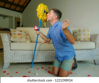 funny portrait of young weird crazy and happy man holding mop with sunglasses as if it was his fiance kneeling and proposing marriage offering engagement ring in wedding proposal parody