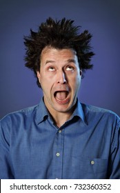 Funny Portraits of a guy who has been electrified: hair standing up with different facial expression on blue background