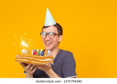 Funny positive guy in glasses holds in his hands a homemade cake with the inscription happy birthday posing on a yellow background with copy space. Concept of holidays and anniversaries.