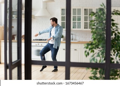 Funny positive man dancing in modern kitchen alone, moving to favorite popular music, celebrating relocation or weekend, happy handsome guy having fun at home, enjoying leisure time