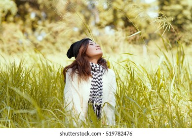 Funny positive young girl in winter white dress  smiling and having fun on natural background in park