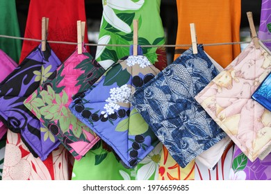 Funny pot holders with fish and pig patterns hanging on a cord with other handmade colorful fabric pot holders at Hilo farmers market, Big island, Hawaii, close up, blurred background