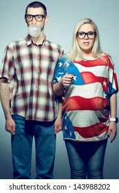 Funny pregnancy concept: portrait of two hipsters (husband and wife) in trendy glasses and clothes playing with their bubble gums. Studio shot