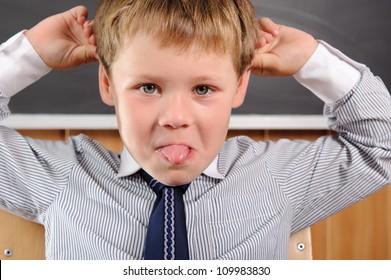 Funny preschool aged boy fooling in classroom