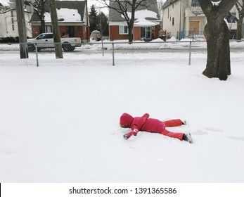 Funny preschool child girl in warm clothes pink red jacket lying in snow during cold winter day with her face down. Upset kid doesn't want to go to school. Naughty cranky kid playing outdoors.
