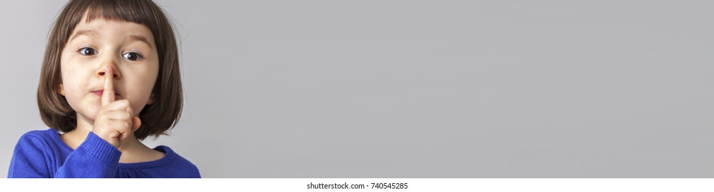 funny preschool girl wanting to keep silent with her finger on lips, grey long copy space banner