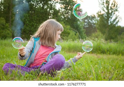 Funny preschooler girl making magic with soap bubbles sitting in a summer park