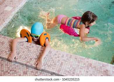 Funny preschoolers boys and girl in bright bathing suits and swimming goggles swim dive in home pool.