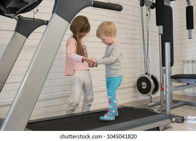 Funny preschoolers of twins boys and girls play and jump on sports simulators. Happy children twins a boy and a girl are having fun together.