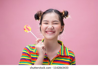 Funny pretty asian girl holding a candy on pink background