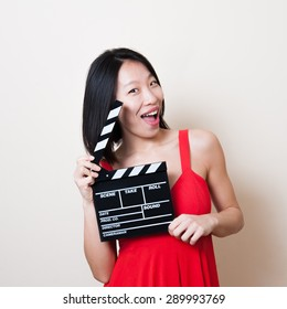 Funny pretty asian woman with red dress and movie clapperboard on white background