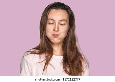Funny pretty girl puffing out her cheeks against lavender studio background. Headshot of charming red haired young woman making mouths while having fun indoors. People, lifestyle, youth and happiness.