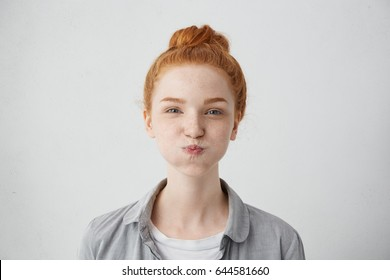 Funny pretty girl puffing out her cheeks against studio wall background. Headshot of charming red haired young woman making mouths while having fun indoors. People, lifestyle, youth and happiness