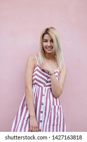 Funny pretty young blond woman in a pink fashionable striped sundress with a positive smile poses near the vintage pink wall outdoors in the city on a summer day. Cute cheerful girl enjoys a walk.