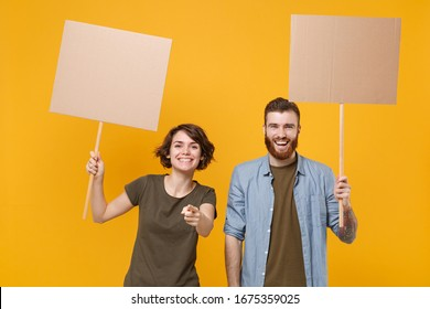 Funny protesting two people guy girl hold protest signs broadsheet blank placard on stick pointing finger on camera isolated on yellow background. Protests strikes pickets concept. Youth against city