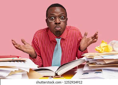 Funny puzzled black male wonk spreads palms with hesitation, blows cheeks and makes griamce, has fun as being tired of cramming material, has hard working day, sits at table with opened book, papers