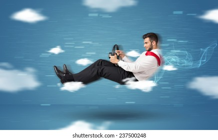 Funny racedriver young man driving between clouds concept on blue background