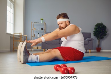 Funny red fat man doing exercises on the floor while standing at home.