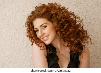 Funny red-haired woman posing in the background. Happy girl with facial expressions, black jumpsuit, curly .