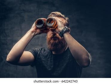 Funny redhead bearded male looking through two craft beer bottle like through binoculars.