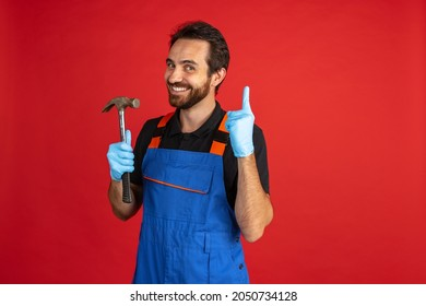 Funny repairing. One young bearded man, male auto mechanic or fitter wearing blue work dungarees isolated over red studio background. Concept of funny meme emotions, ad, job, insipation, ideas, sales