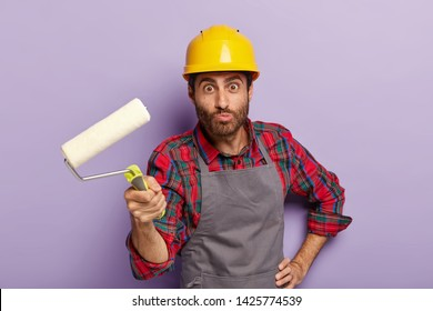 Funny repairman wears hardhat, apron, holds paint roller in hand for painting wall in purple color. Craftsman uses special tool, isolated over purple background. Building, repairing and construction
