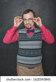 Funny retro style teacher in eyeglasses looking at you on blackboard background