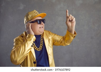 Funny rich senior man in golden jacket playing music at disco party. Studio shot of happy old grandpa in baseball cap and bling chain necklace enjoying leisure time and mixing songs on DJ turntable