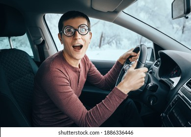 Funny and ridiculous idiotic nerd driver in big eyeglasses holding the steering wheel and smiling to the camera. Concept of a newbie driver distracted from the road