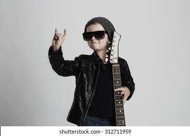 Funny rock child with guitar. fashionable little boy in sunglasses. stylish kid in leather coat. music concept