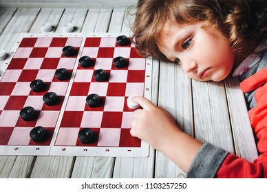 The funny sad little red haired child plays checkers. Children's hand on a checkerboard. Play board games. Loss, defeat, deadlock.