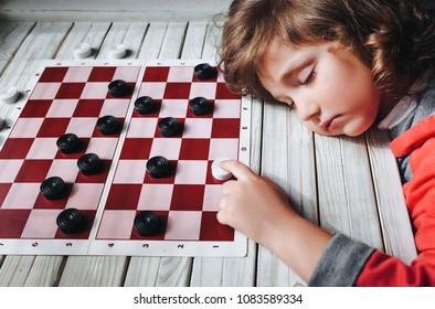 The funny sad red haired child plays checkers. Children's hand on a checkerboard. Play board games. Loss, defeat, deadlock.