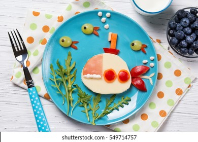 Funny sandwich with cheese in a shape of submarine and fishes, meal for kids idea
